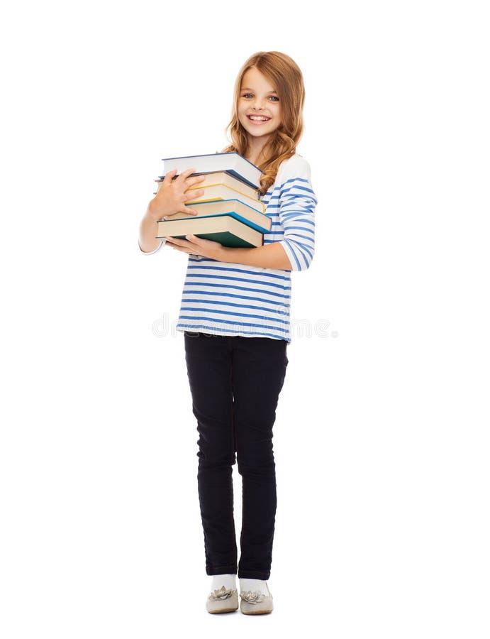 Маленькая девушка студента с много книг стоковое фото