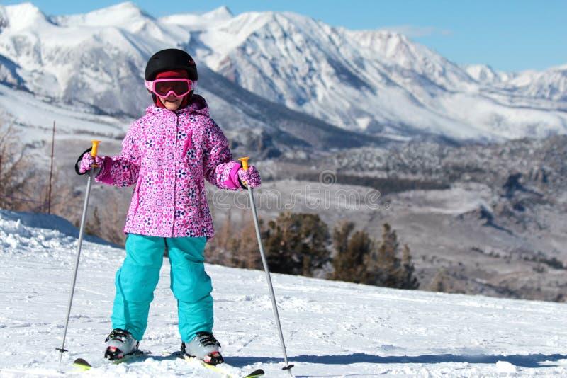 Маленькая девушка лыжника на лыже горы стоковое фото