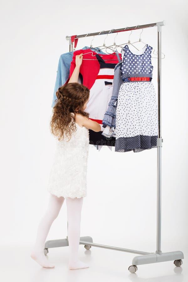 Маленькая женщина пробуя новую одежду на белой предпосылке стоковые изображения