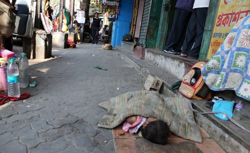 Маленькая индийская девушка спать на улице, Kolkata стоковое изображение rf