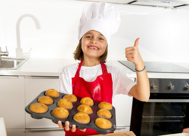 Маленькая и милая девушка самостоятельно в шляпе и рисберме кашевара представляя и показывая поднос с усмехаться булочек счастлив стоковые изображения