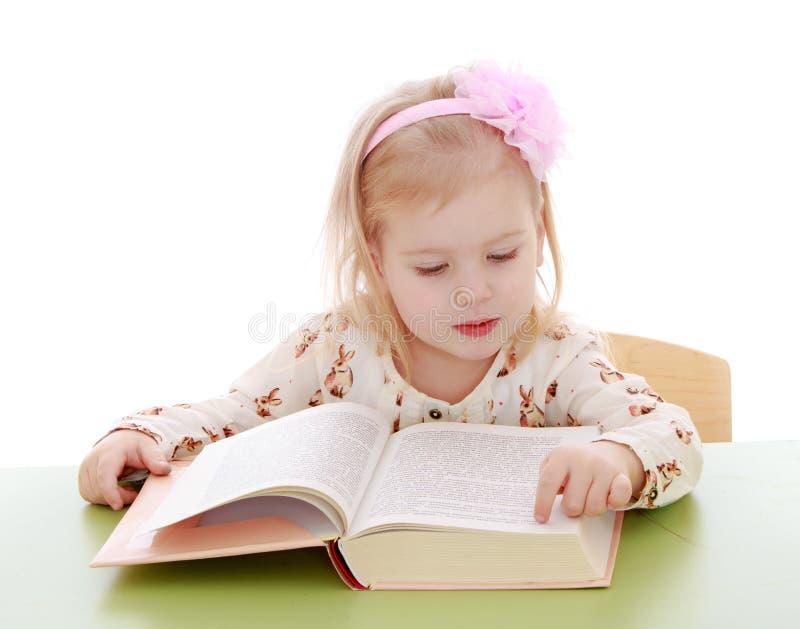 Маленькая кавказская белокурая девушка сидя на столе и стоковое изображение rf