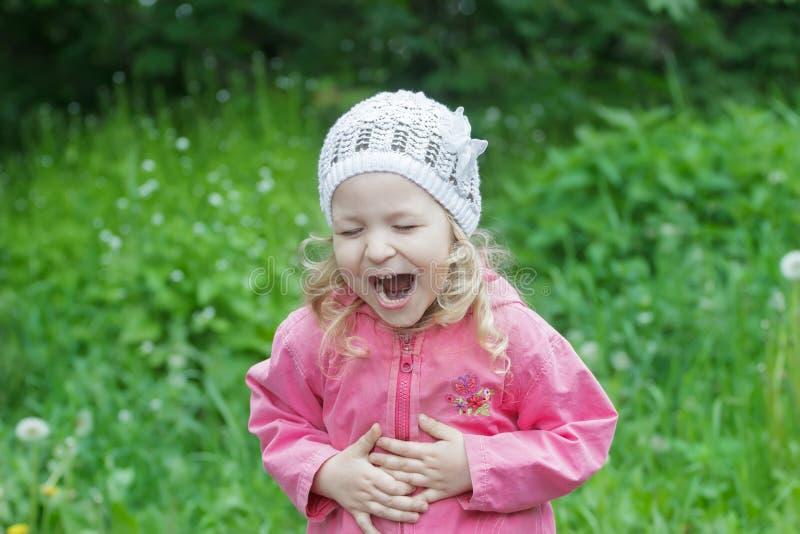 Маленькая кавказская девушка гнуть с садом зеленого цвета хохота живота весной стоковое изображение