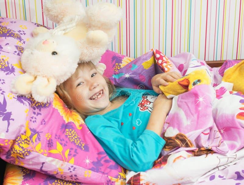 Маленькая красивая девушка в кровати стоковая фотография