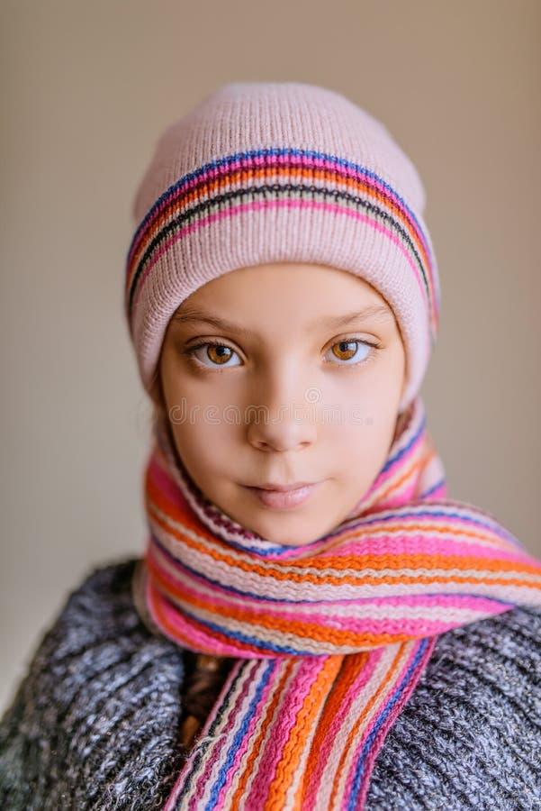 Маленькая красивая девушка в шляпе и шарфе зимы стоковые фото