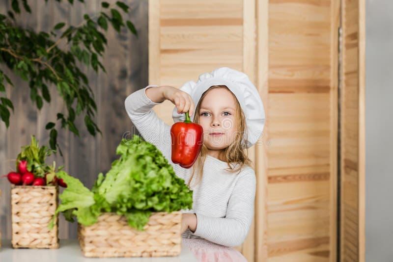 Маленькая красивая девушка делая vegetable салат в кухне еда здоровая домохозяйка немногая стоковые изображения