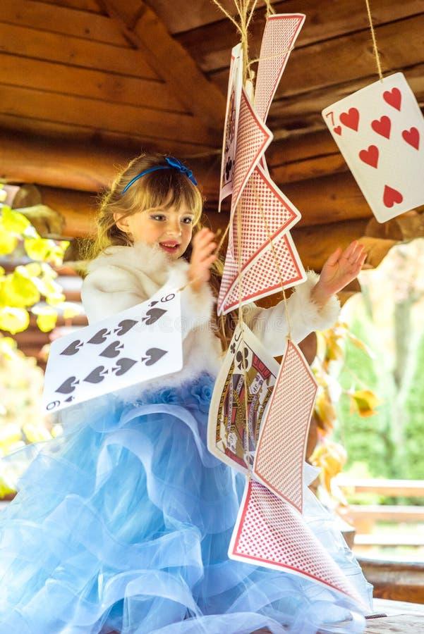 Маленькая красивая девушка играя и танцуя с большими играя карточками на таблице стоковые изображения rf