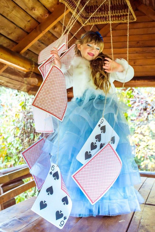 Маленькая красивая девушка играя и танцуя с большими играя карточками на таблице стоковое изображение rf