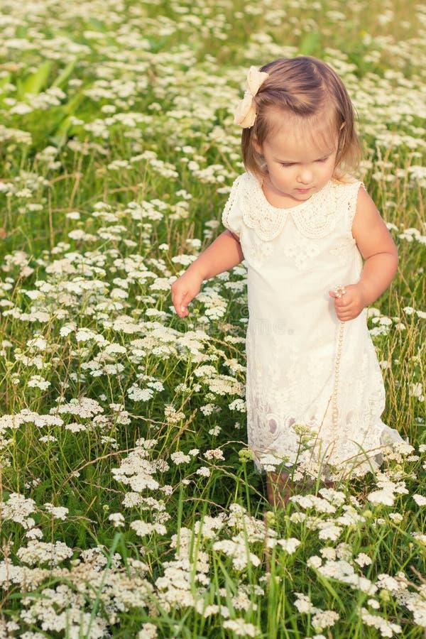 Маленькая красивая девушка идет в поле цветков в белом платье на солнечный летний день стоковое изображение