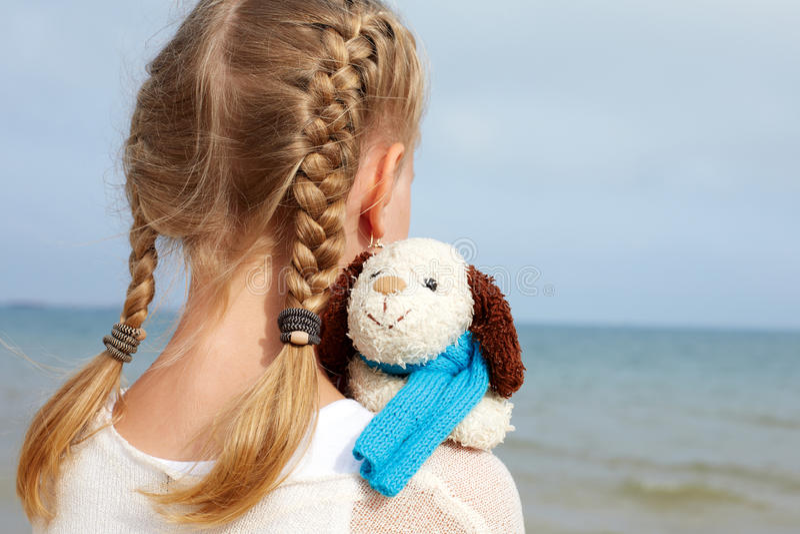 Маленькая красивая девушка обнимает забавную собаку - игрушку стоковые изображения rf