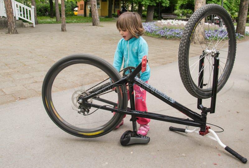Маленькая красивая девушка ремонтируя велосипед в парке стоковое фото