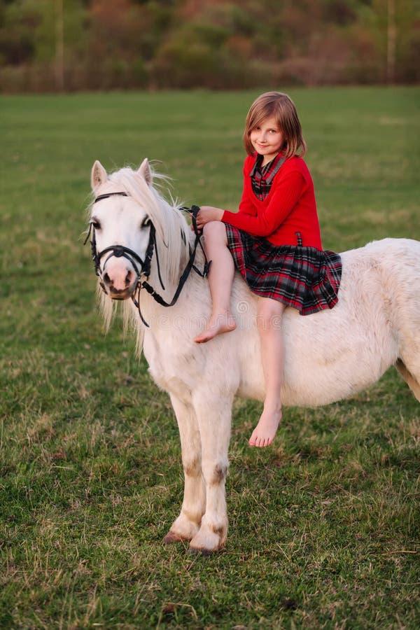 Маленькая маленькая девочка в платье сидя на даме катания пони стоковые фотографии rf
