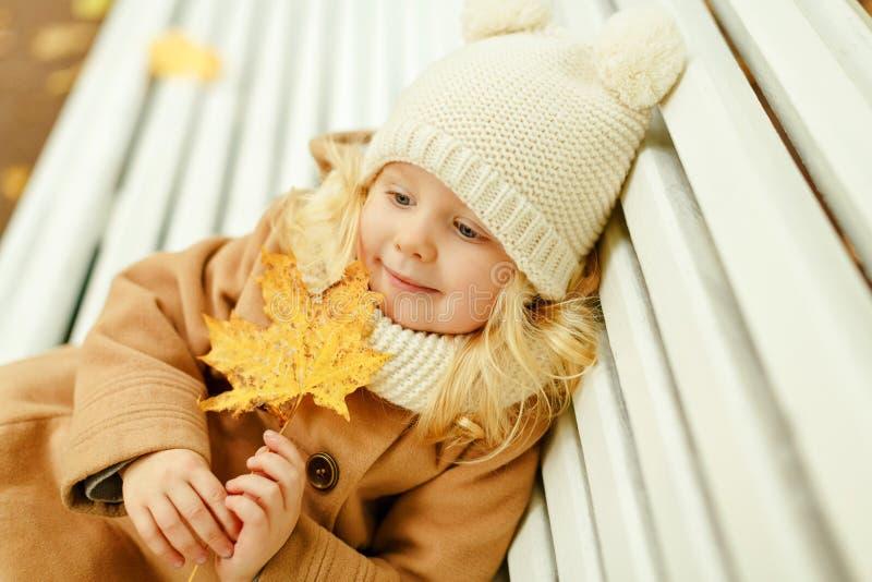 Маленькая милая девушка в бежевом пальто сидя на стенде и holdin стоковая фотография rf