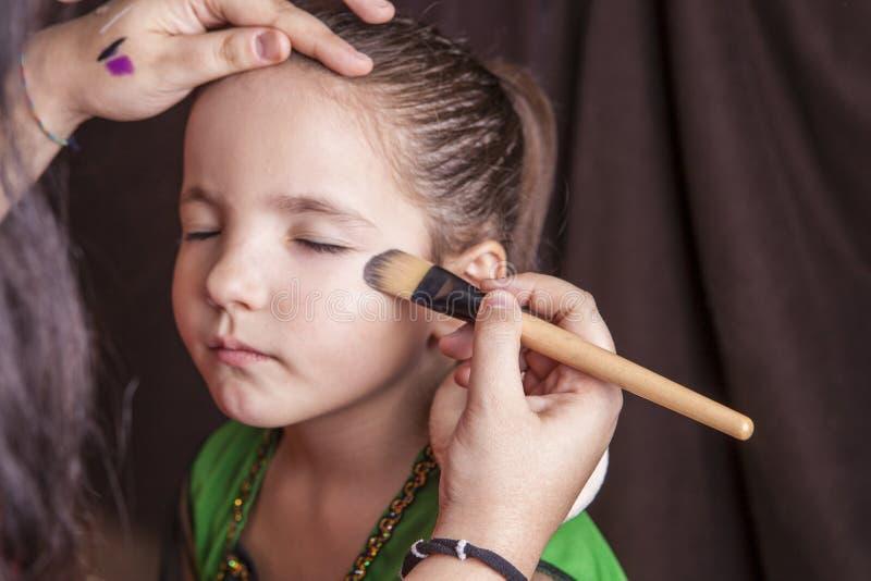 Маленькая милая девушка делая facepaint перед партией хеллоуина стоковая фотография