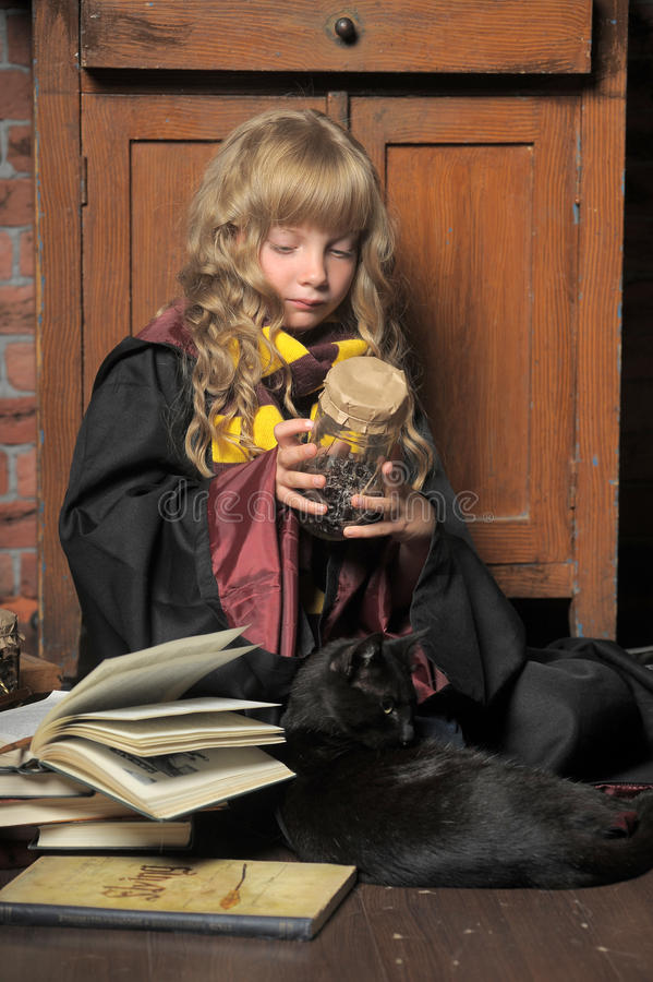 Маленькая молодая ведьма с черным котом и книгами стоковые изображения