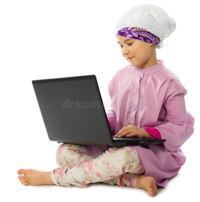 Маленькая мусульманская девушка с компьтер-книжкой стоковые изображения rf