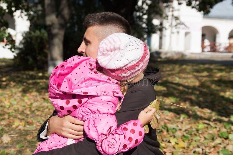 Маленькая дочь обнимая ее отца стоковое изображение rf