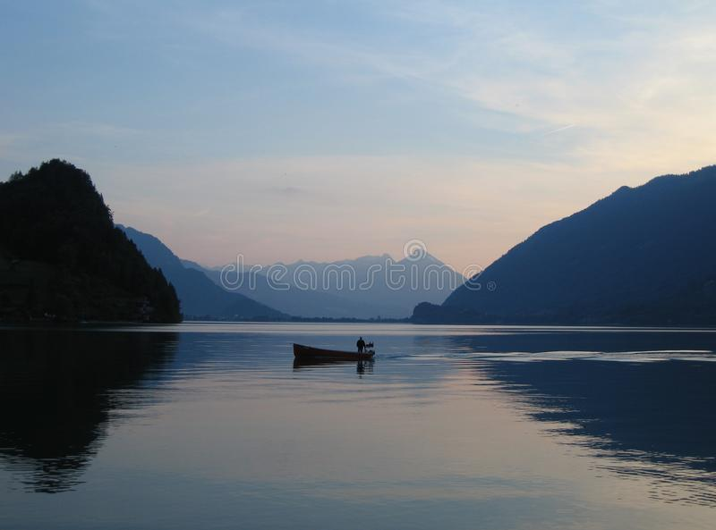 Маленькая лодка на неподвижных водах Brienzersee, Швейцарии на заходе солнца стоковые изображения rf