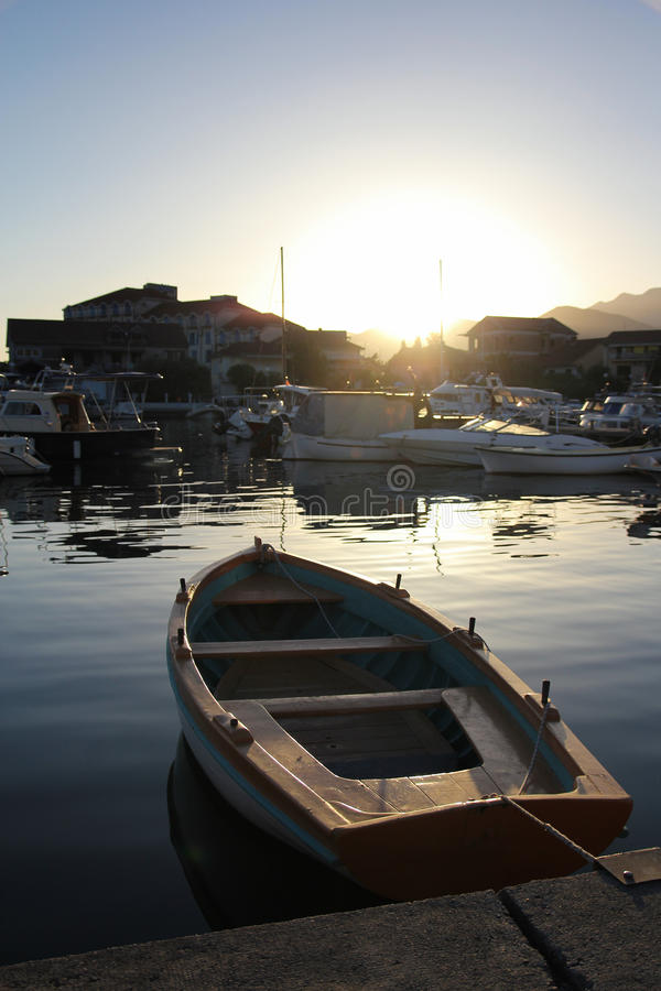 Маленькая лодка на драматическом заходе солнца в Tivat стоковые фото