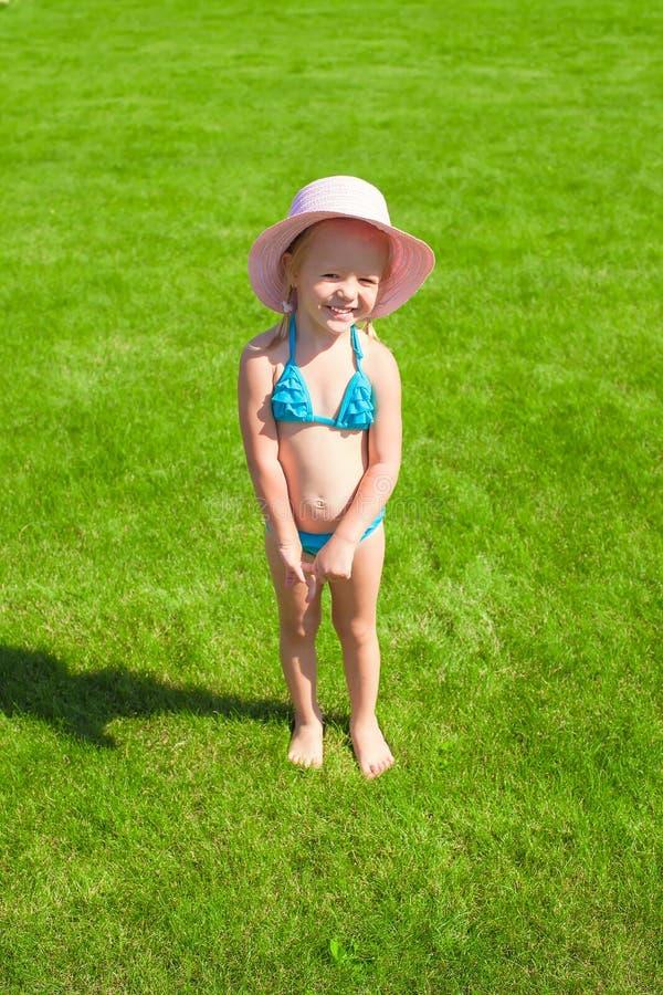 Маленькая прелестная девушка в играть купальника внешний стоковая фотография rf