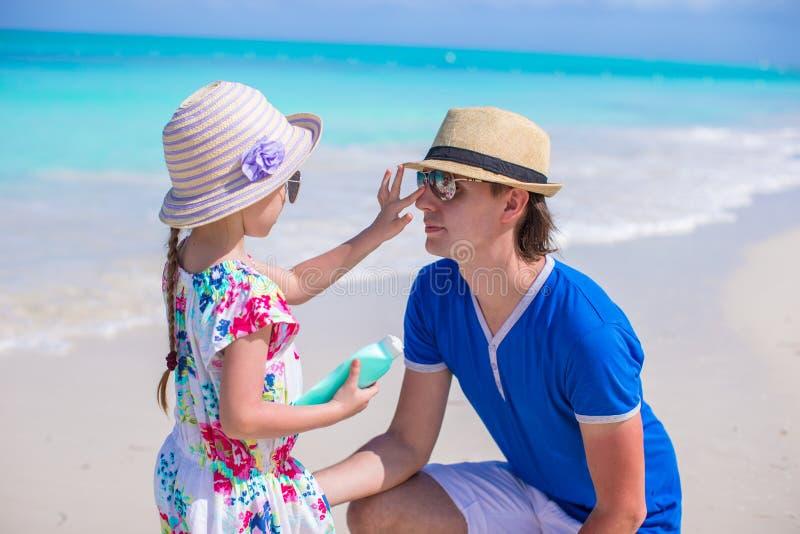 Маленькая прелестная девушка прикладывая сливк солнца к ее носу отца стоковые фотографии rf