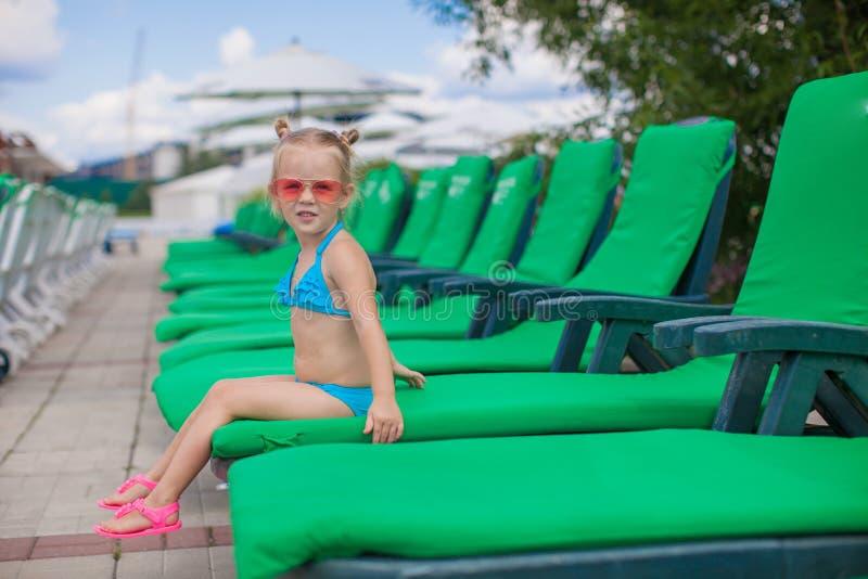 Маленькая счастливая девушка на loungers смотреть бассейна стоковая фотография