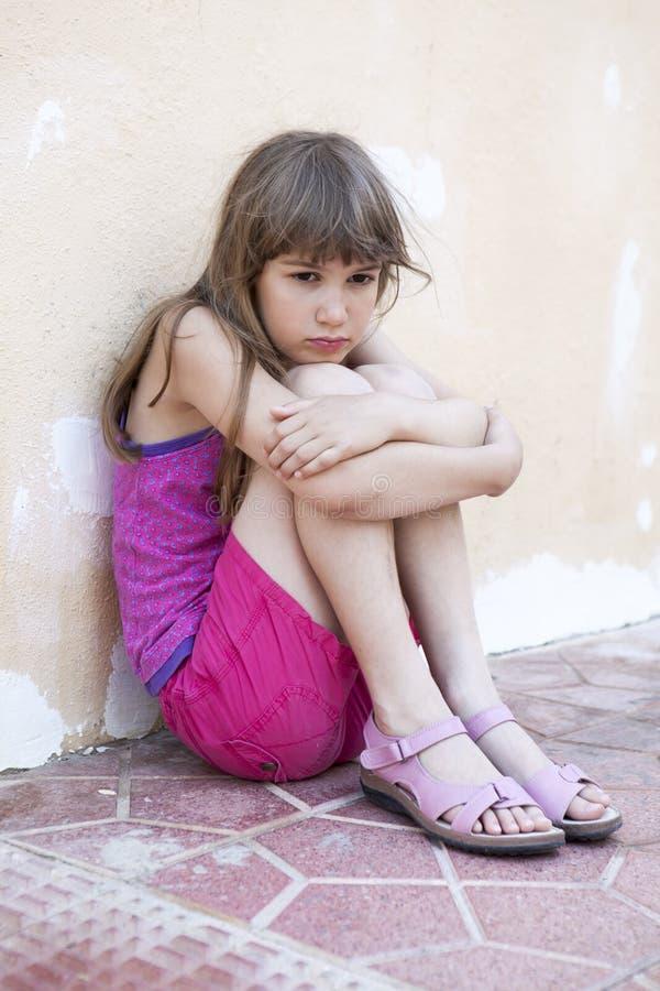 Маленькая унылая девушка при длинные волосы сидя обнимающ ее колени стоковые изображения