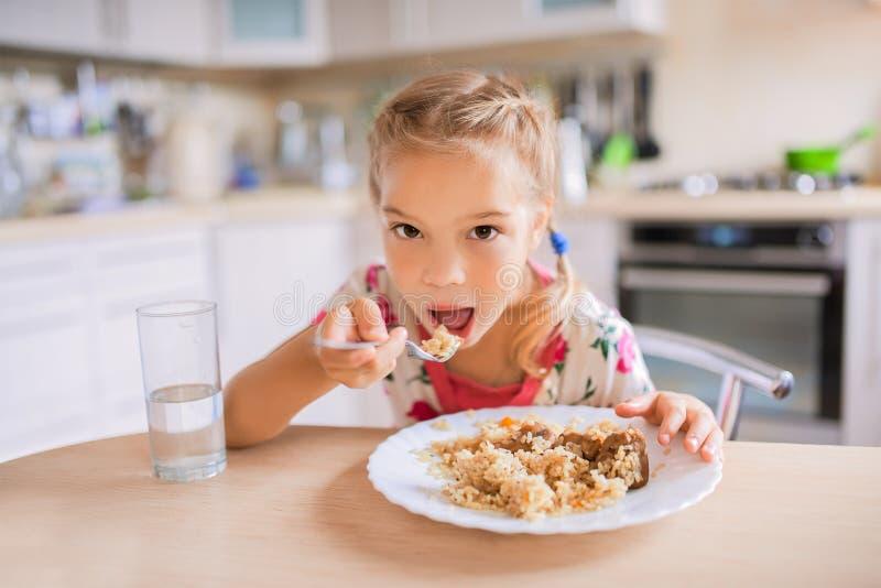 Маленькая унылая девушка сидит на таблице и ест pilaf стоковое изображение rf
