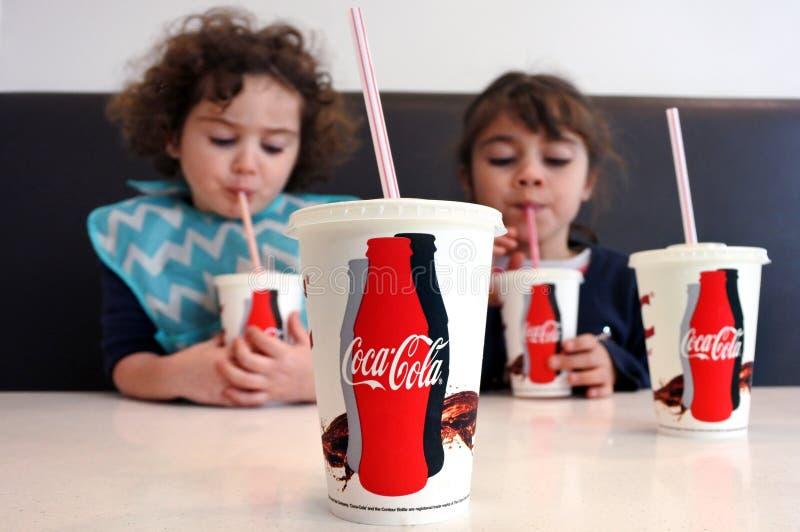 Маленькие девочки выпивая кока-колу стоковые фотографии rf