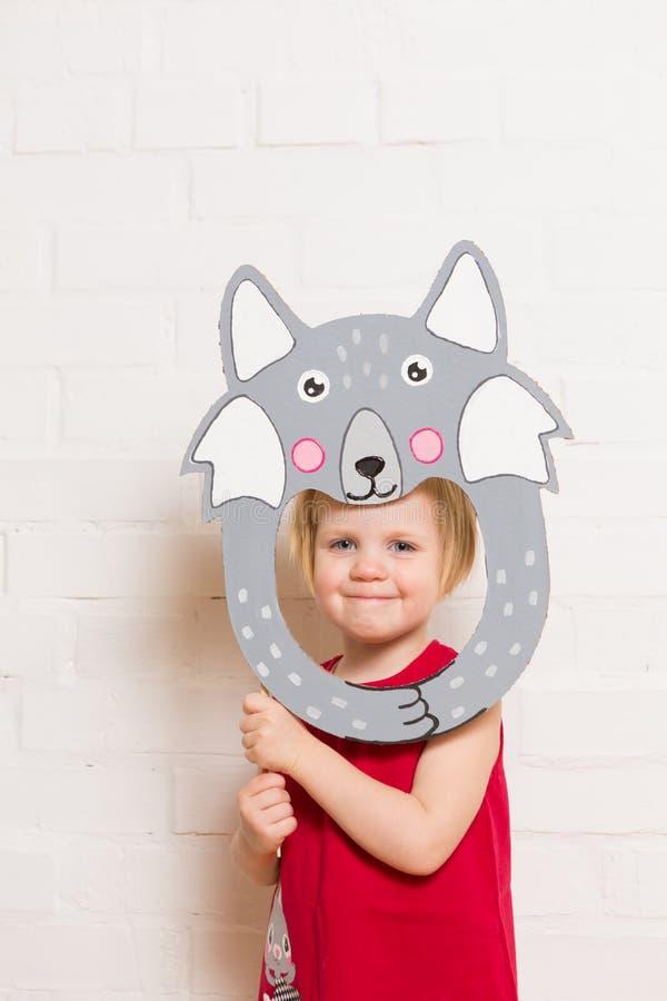 Маленькие девочки держа маску волка на белой предпосылке стоковое фото
