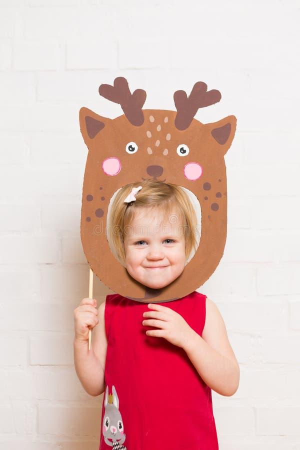 Маленькие девочки держа маску оленей на белой предпосылке стоковое фото