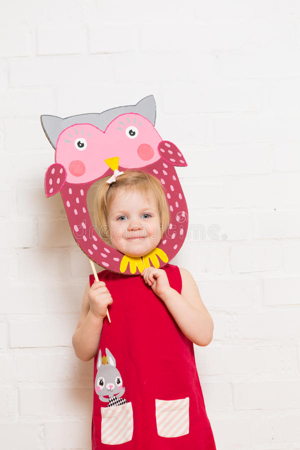 Маленькие девочки держа маску сыча на белой предпосылке стоковое изображение