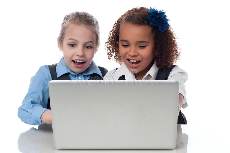 Маленькие девочки играя игры на компьтер-книжке стоковое фото rf