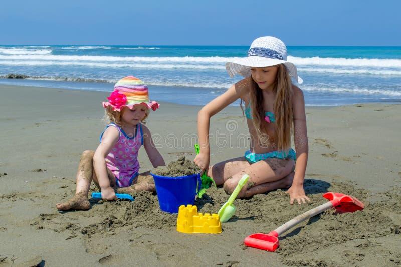 Маленькие девочки играя на пляже стоковая фотография rf