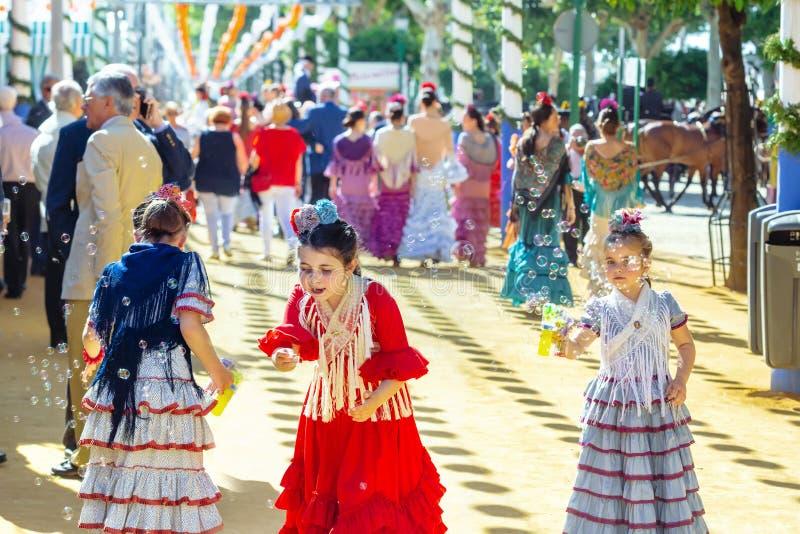Маленькие девочки играя с пузырями мыла на ярмарке ` s апреля Севильи стоковые фотографии rf