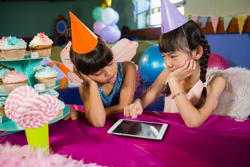 Маленькие девочки используя таблетку на партии стоковая фотография rf