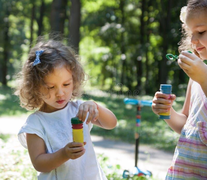 Маленькие девочки и пузыри мыла стоковые фотографии rf