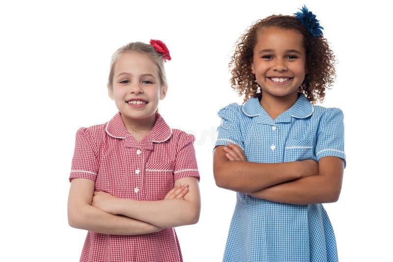 Маленькие девочки представляя при пересеченные оружия стоковое фото