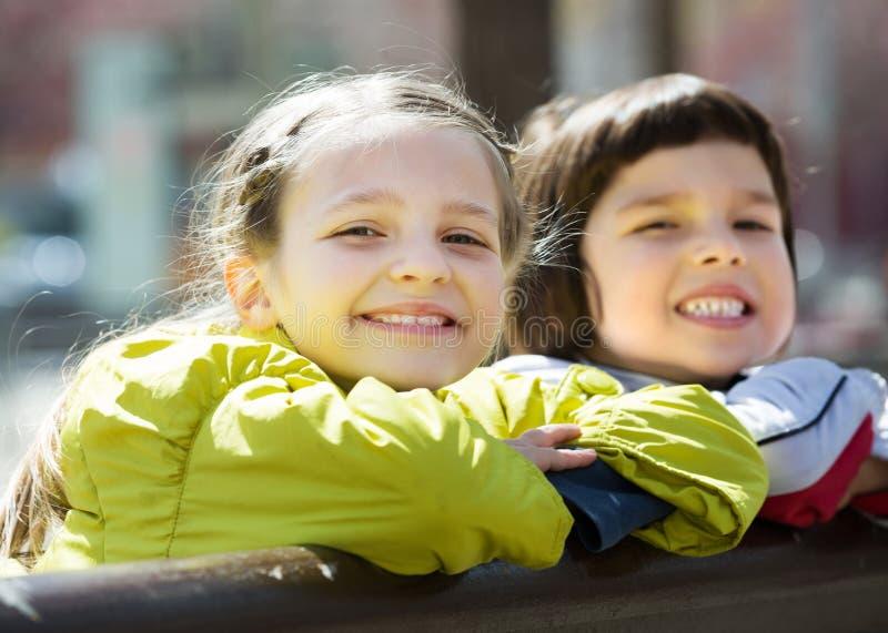 Маленькие девочки прижимаясь и усмехаясь стоковые изображения