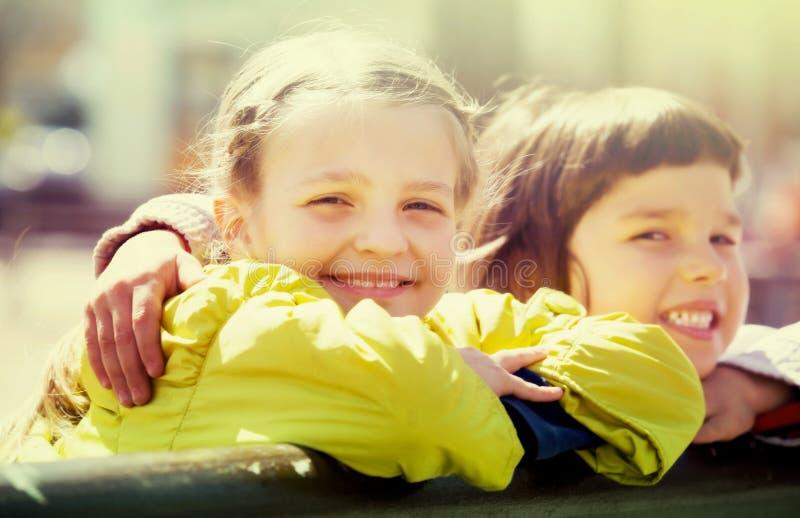 Маленькие девочки прижимаясь и усмехаясь стоковая фотография
