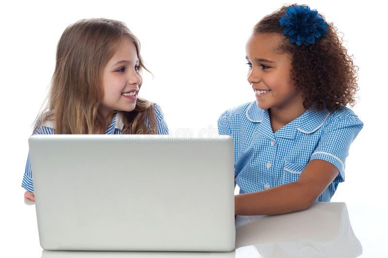 Маленькие девочки уча в компьтер-книжке стоковые фото