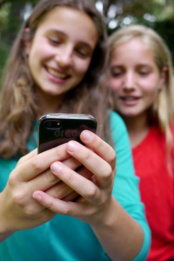 Маленькие девочки читая текстовое сообщение стоковое изображение