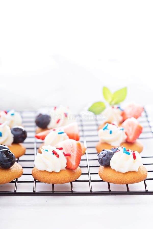 Маленькие десерты с взбитыми сливк и ягодами стоковая фотография rf