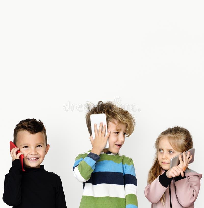 Маленькие дети говоря на технологии телефона стоковая фотография rf