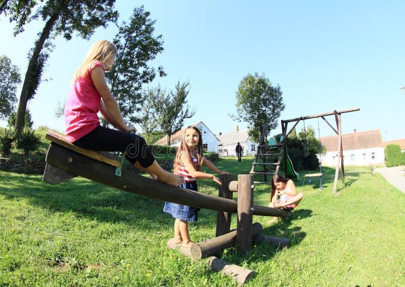 Маленькие ребеята играя на деревянном качании стоковое изображение rf