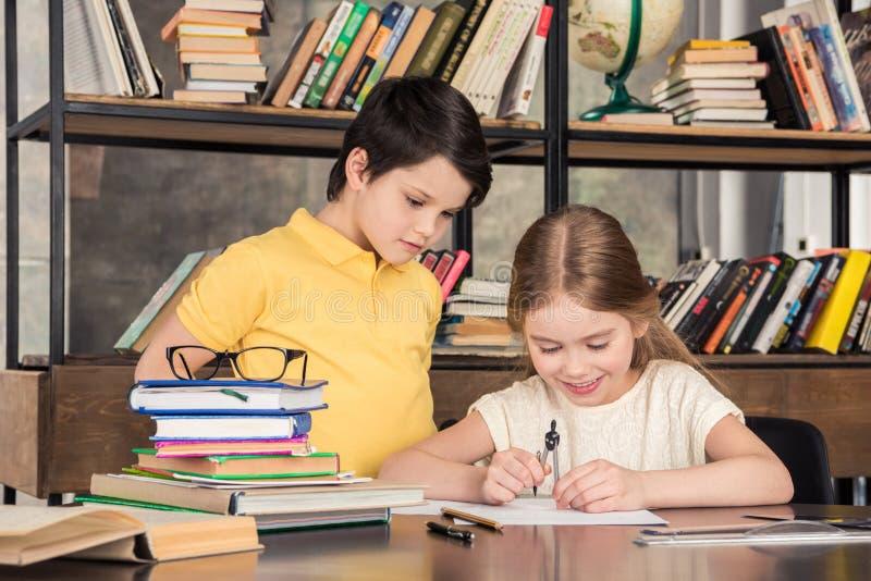 Маленькие школьники изучая в библиотеке совместно стоковые изображения