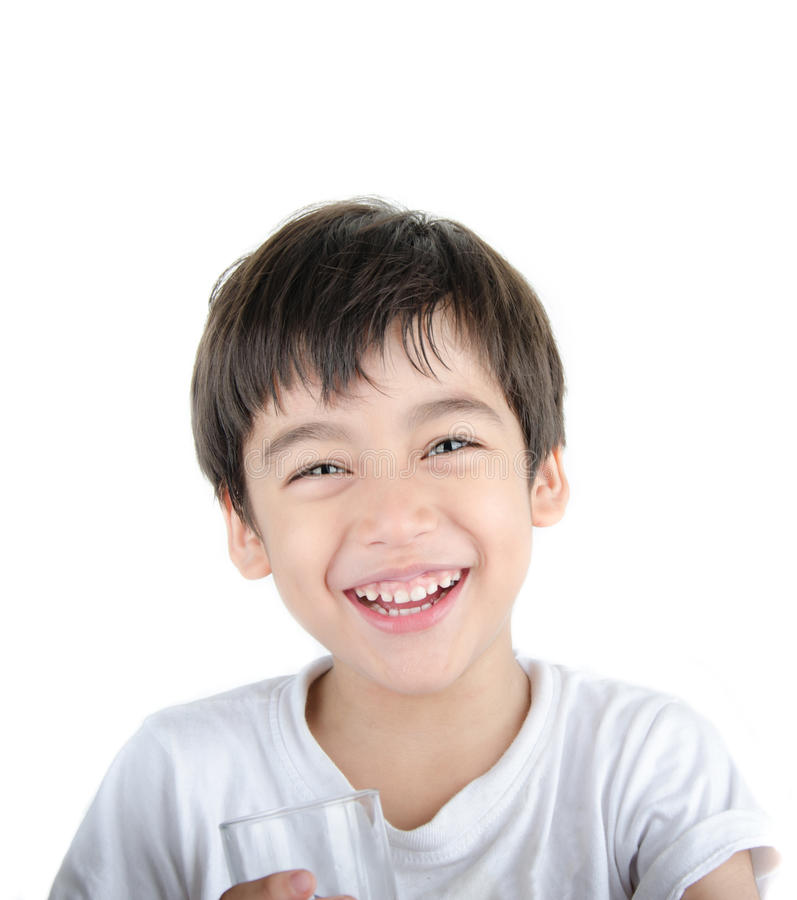 Маленький азиатский мальчик выпивает воду от стекла на белой предпосылке стоковое изображение