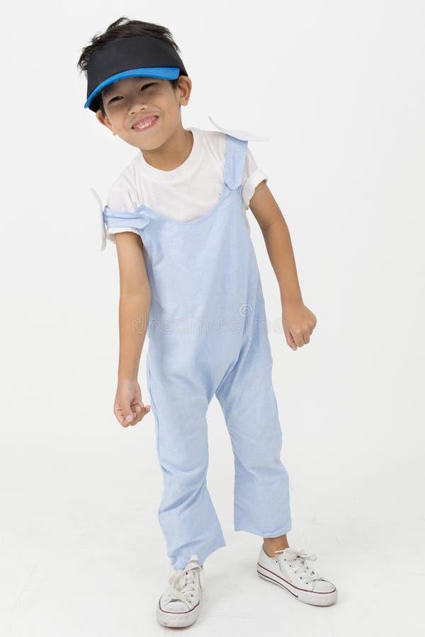 Маленький азиатский мальчик в винтажном костюме скачки с стороной улыбки стоковая фотография