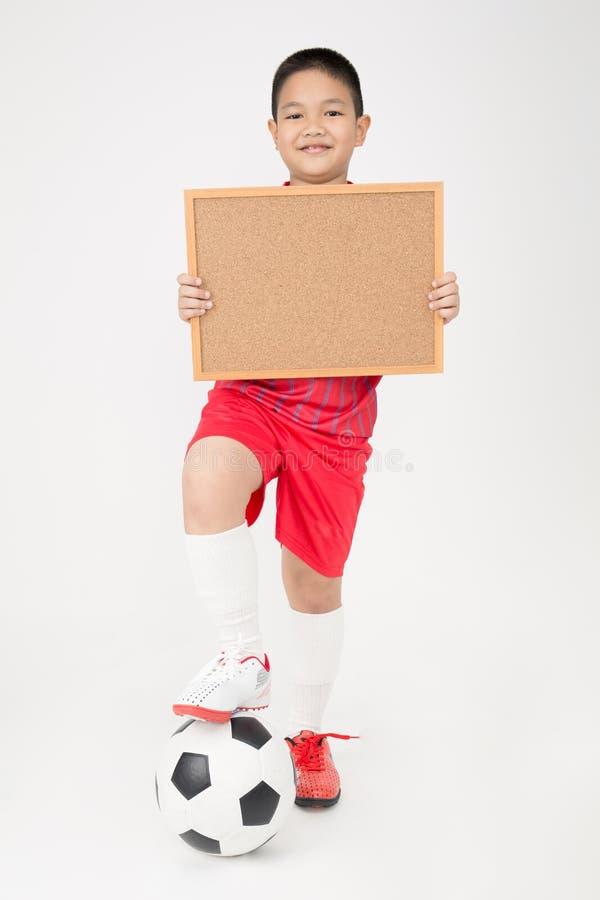 Маленький азиатский мальчик держа пустую деревянную доску в форме спорта стоковое фото rf