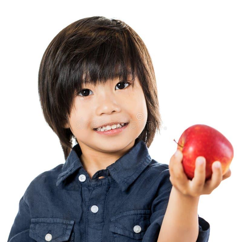 Маленький азиатский мальчик показывая красное яблоко стоковые фото